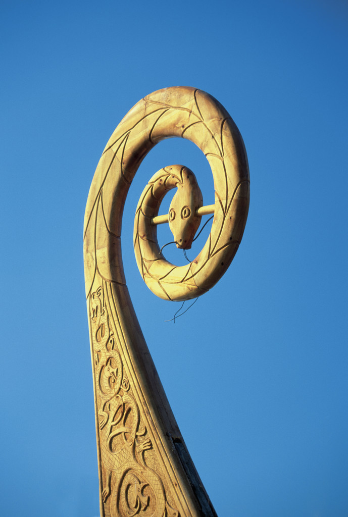 Upper part of a carved wooden figurehead from a Viking ship against a blue background Oslo, Norw