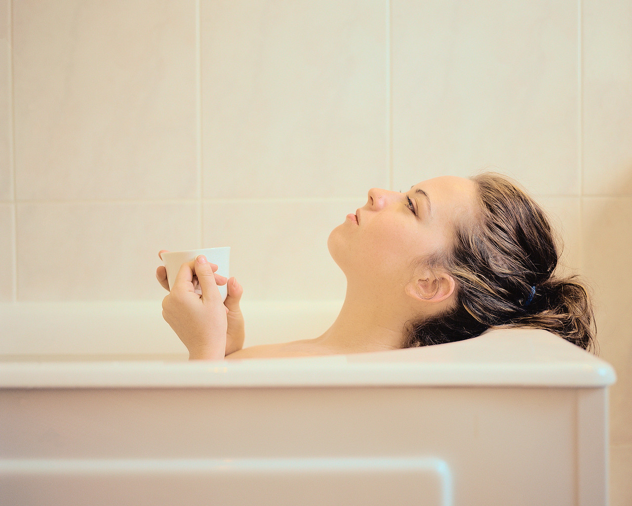 Woman Lying in a Bathtub Holding a Mug